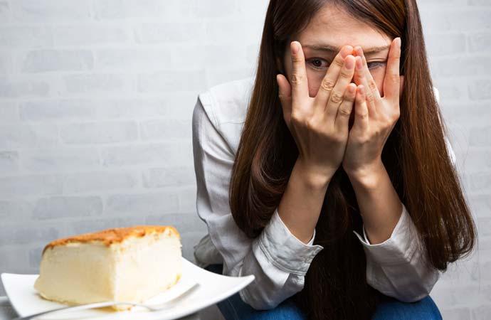 ダイエットをしていて甘い物を我慢している女性